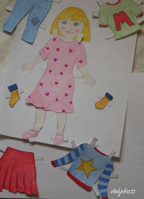 Magda, die Anziehpuppe, probiert ein Kleid an